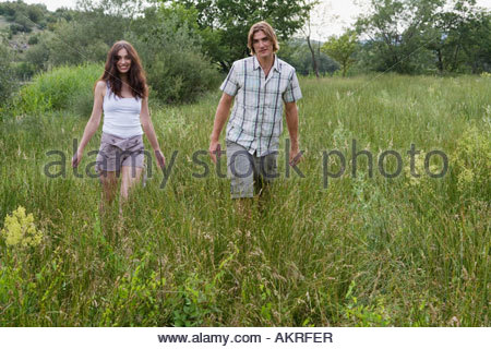 Young couple walking in a field - Stock Photo