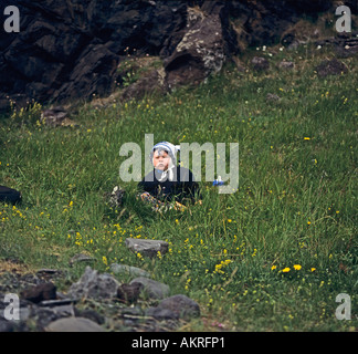 ICELAND EUROPE July Ten month old Icelandic boy with chubby red cheeks sitting in the grass - Stock Photo