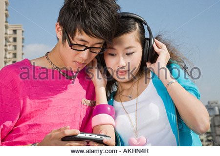 Teenagers with video game and headphones - Stock Photo
