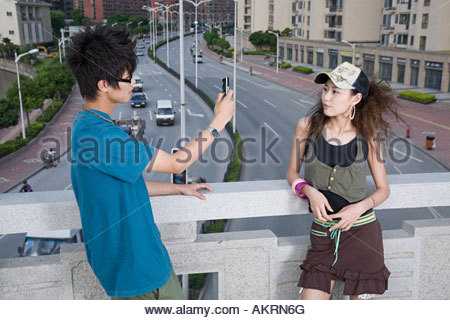Teenage couple with camera phone - Stock Photo