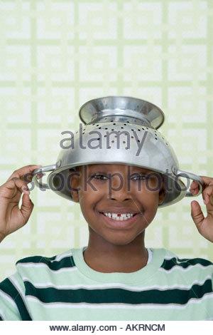Boy wearing a colander - Stock Photo