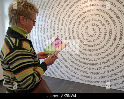woman looking a drawing with the endless number of Pi in form of a helix on the wall in the museum Mathematikum - Stock Photo