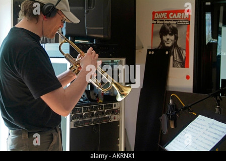 working in recording studio musician with musical instrument trumpet trump playing in a studio - Stock Photo