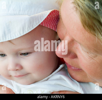 grandmother and grandchild portrait of a baby of 8 months with sun hat and a woman in age of about 45 to 55 years - Stock Photo