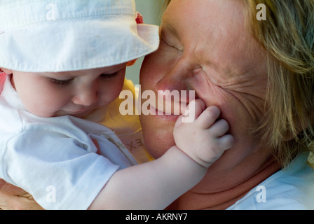 grandmother and grandchild baby of 8 months with sun hat and a woman in age of about 45 to 55 years - Stock Photo