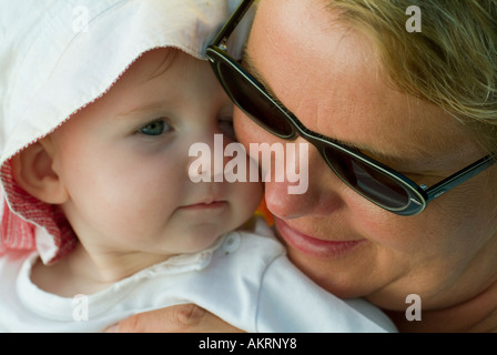 grandmother and grandchild baby of 8 months with sun hat and a woman in age of about 45 to 55 years with sunglasses - Stock Photo