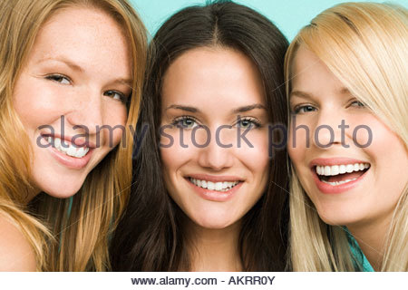 Three beautiful young women in a row - Stock Photo