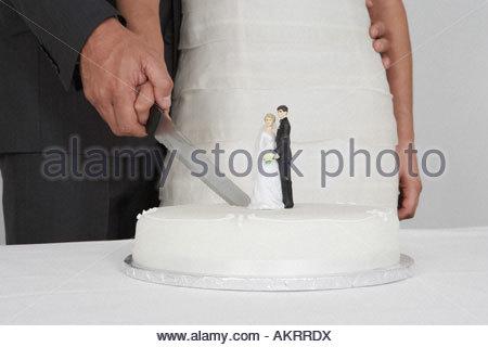 Newlyweds cutting the wedding cake - Stock Photo