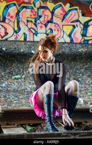 Goth girl sitting on railroad tracks in front of graffiti - Stock Photo