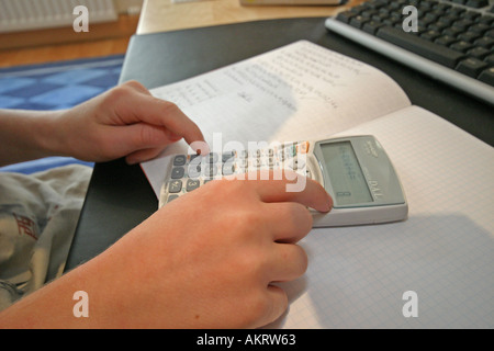 boy doing maths with his calculator in his bedroom - Stock Photo