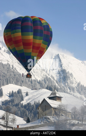 Hot Air Balloon by Church in the Alps during International Hot Air Balloon Week Chateau d Oex Switzerland - Stock Photo