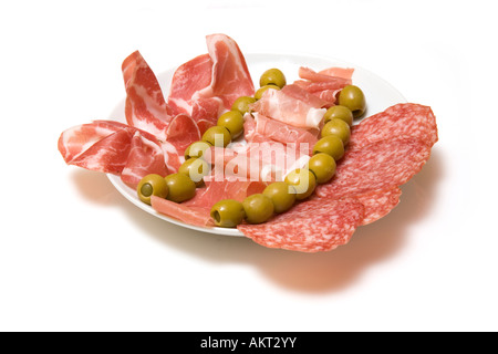 Plate of mixed tapas cured meats and olives isolated on a white studio background. - Stock Photo