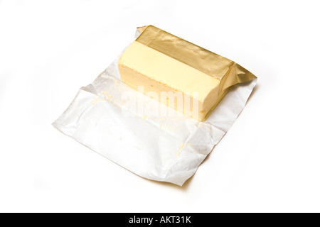 Slab of traditional butter with foil wrapper isolated on a white studio background. - Stock Photo