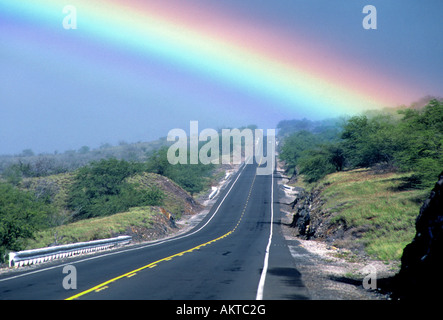 A view of the Kona Coast Highway with a rainbow just after a rainstorm - Stock Photo