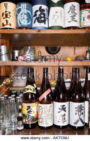 Bottles of sake on a shelf in a bar - Stock Photo