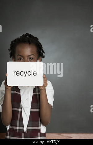 Girl with sign saying recycle - Stock Photo