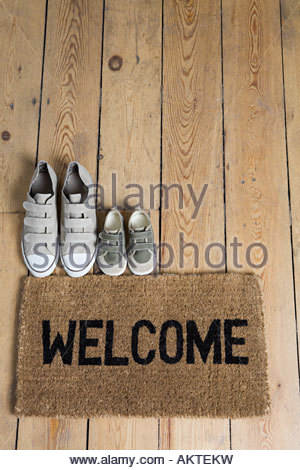 Training shoes and a welcome mat - Stock Photo