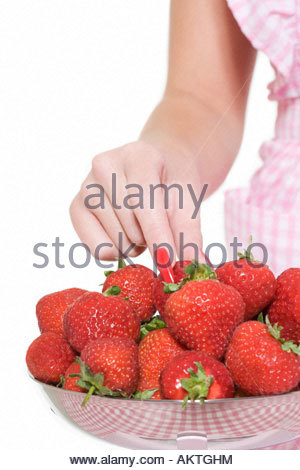 Woman taking a strawberry from bowl - Stock Photo