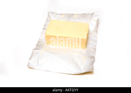 Slab of butter with foil wrapper isolated on a white studio background. - Stock Photo
