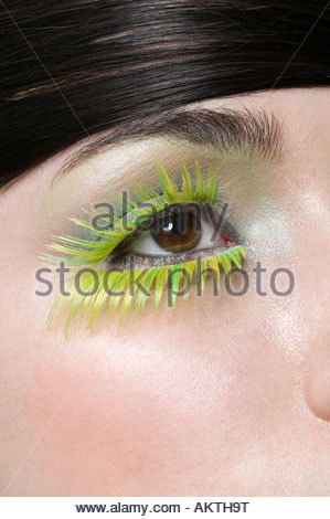 A woman wearing green false eyelashes - Stock Photo