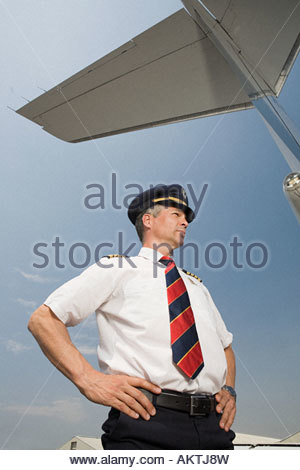 Pilot under airplane tail - Stock Photo