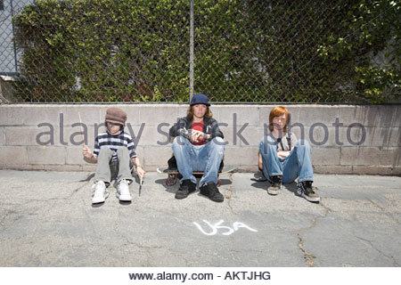 Portrait of boys sat in a street - Stock Photo