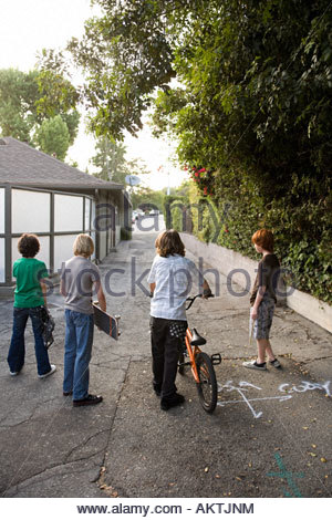 Rear view of boys stood in a street - Stock Photo