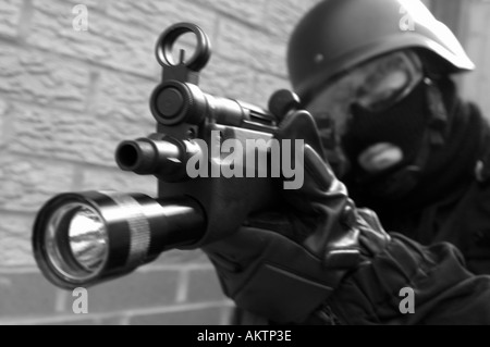a swat police officer in full uniform with helmet and mp5 machine gun - Stock Photo