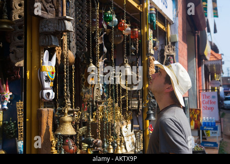 INDIA KERALA FORT COCHIN TOURIST LOOKING AT SOUVENIRS IN GIFT SHOP - Stock Photo