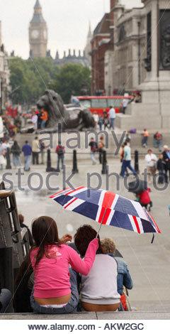 A Union Jack umbrella in Trafalgar Square, looking towards Big Ben and Parliament. London England - Stock Photo