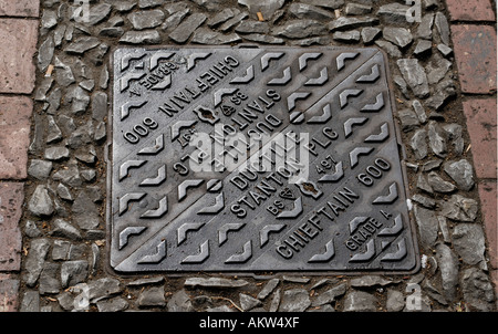Iron manhole cover in two halves made by Ductile Stanton and Staveley The Chieftain - Stock Photo