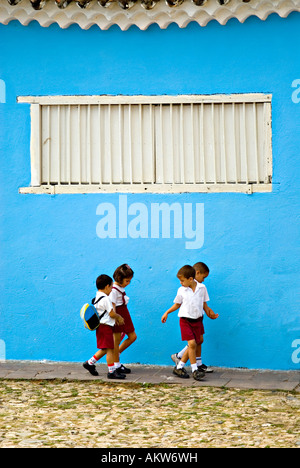 Cuban school children walk together between lessons on the cobbled streets of Trinidad de Cuba - Stock Photo