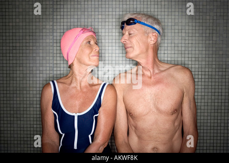 Senior couple in changing room, wearing swim cap and goggles - Stock Photo