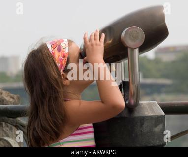 A little girl looks at Niagara Falls through coin operated binoculars, Ontario Canada - Stock Photo