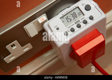 DIGITAL ELECTRONIC TIMER FOR ELECTRICAL APPLIANCES PLUGGED INTO 13 AMP MAINS SOCKET - Stock Photo