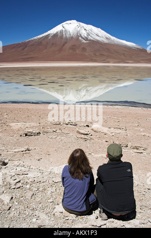 Man and woman sitting, Laguna Verde, Bolivia near the border to Chile, South America - Stock Photo
