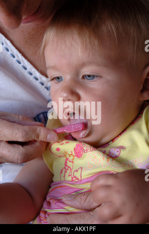 Baby girl having her teeth brushed by her mother - Stock Photo
