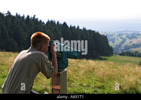 Boy with short cut red hair looking through a fixly mounted telescope. Hoherodskopf mountain, Vogelsberg, Hesse, - Stock Photo