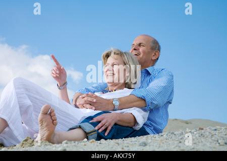 Mature couple sitting on beach - Stock Photo