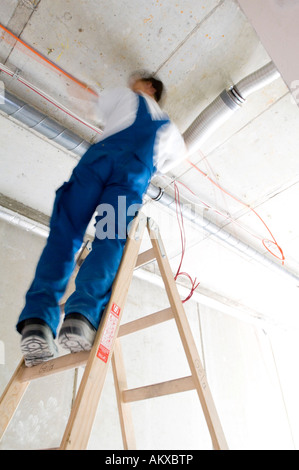 Construction worker lays cables at the ceiling - Stock Photo
