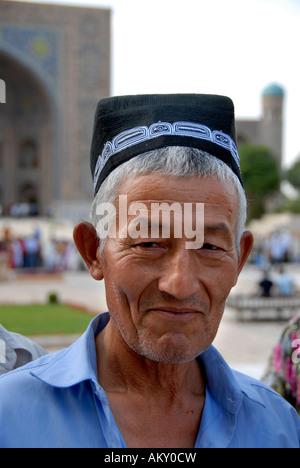 Uzbek man dressed in traditional cloth tubiteka Registan Madrasah Tilla-Kari Samarkand Uzbekistan - Stock Photo