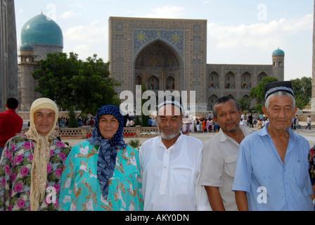 Uzbek people dressed in traditional cloth in front of Registan Madrasah Tilla-Kari Samarkand Uzbekistan - Stock Photo