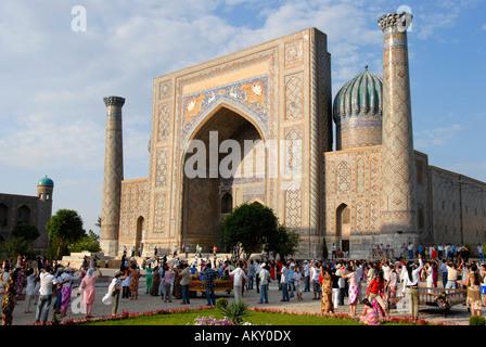 People dancing at Madrasah Sherdar Registan Samarkand Uzbekistan - Stock Photo