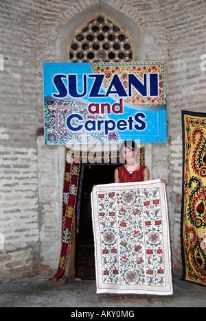 Young Uzbek salesgirl in front of her shop selling suzani and carpets in Madrasah Kukeldash Bukhara Uzbekistan - Stock Photo