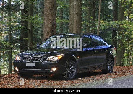 New BMW 535d series in autumn forest - Stock Photo