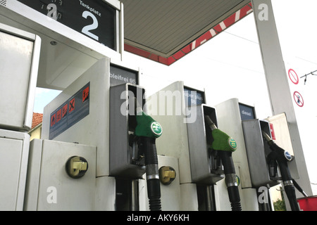 Fuel nozzles at a gas station - Stock Photo