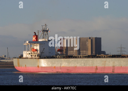 Shipping large merchant ship ore carrier leaving the River Tees estuary Teesside with Hartlepool Nuclear Power station - Stock Photo