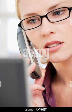 Woman in office using phone, close-up - Stock Photo