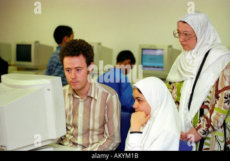 Two young Muslim women learning computer skills with tutor, London, UK. - Stock Photo