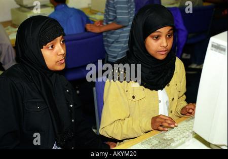 Two young Muslim women learning computer skills, London UK. - Stock Photo